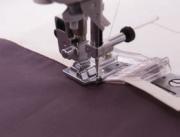 © JUKI Nähmaschinen – Für das Einfassen mit Schrägband von Stoffkanten oder Halsausschnitten wurde dieser Einfasser entwickelt. Somit erhalten Ihre Stoffkanten ein sauberes und glattes Aussehen.